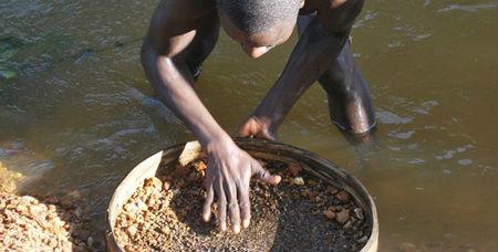 chercheur de diamants au bord d'une rivière